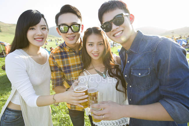 Chinese friends holding beer and looking in camera — Stock Photo