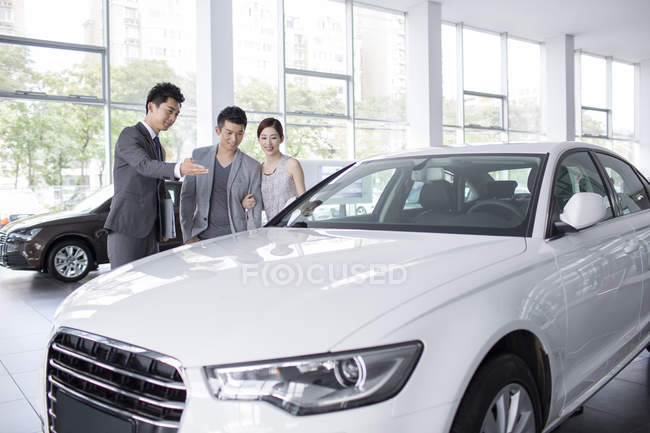 Chinese couple talking with dealer while choosing car in showroom — Stock Photo
