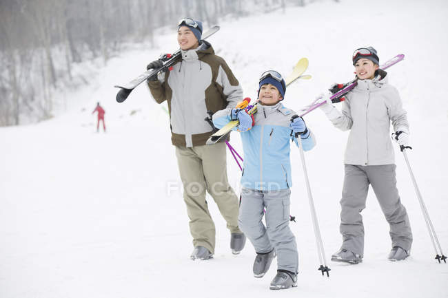 Chinese parents with son walking with skis on shoulders in ski resort — Stock Photo