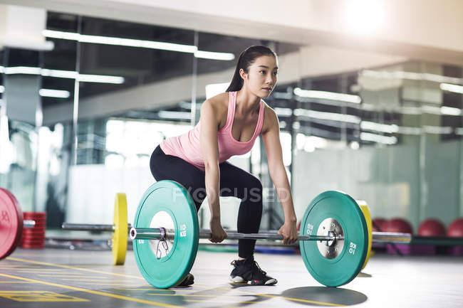 Asian woman lifting barbells at gym — Stock Photo