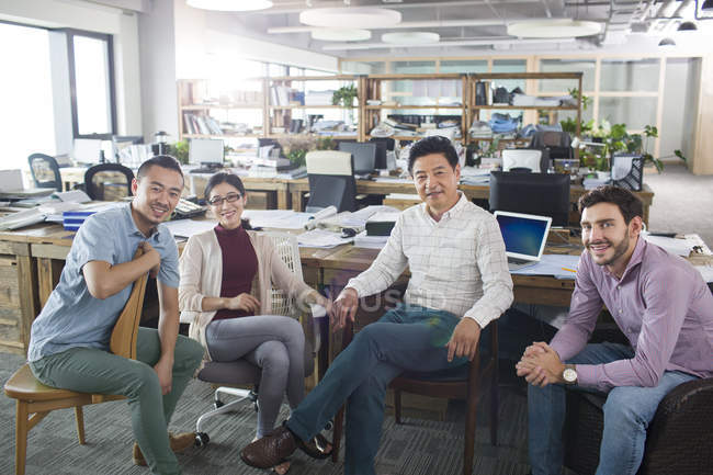 Деловые коллеги сидят в офисе и смотрят в камеру — стоковое фото