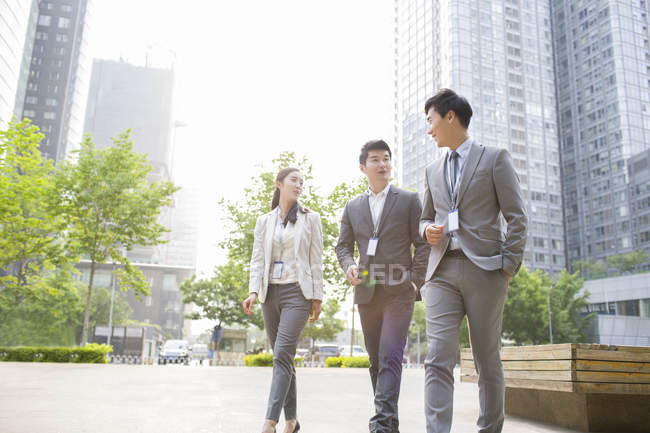 Chinese business people talking on street — Stock Photo