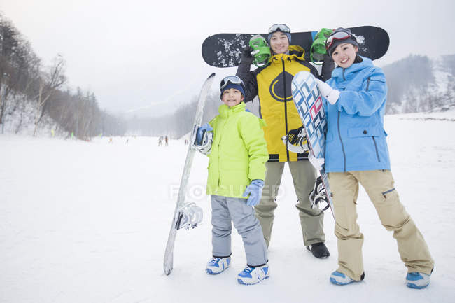 Chinese family holding snowboards on slope — Stock Photo