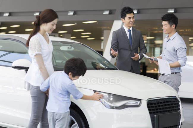 Chinese family examining new car in showroom with car seller — Stock Photo