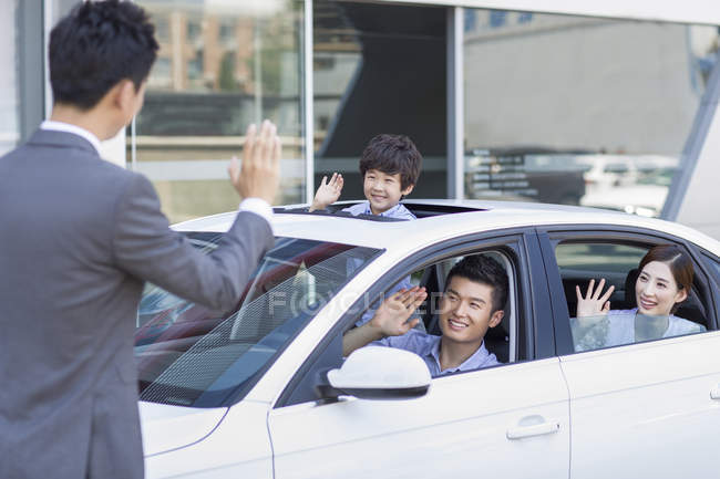 Chinese family sitting in new car waving to car seller — Stock Photo