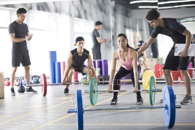 Азиатские спортсменов, работающих с тренеров в тренажерный зал — стоковое фото