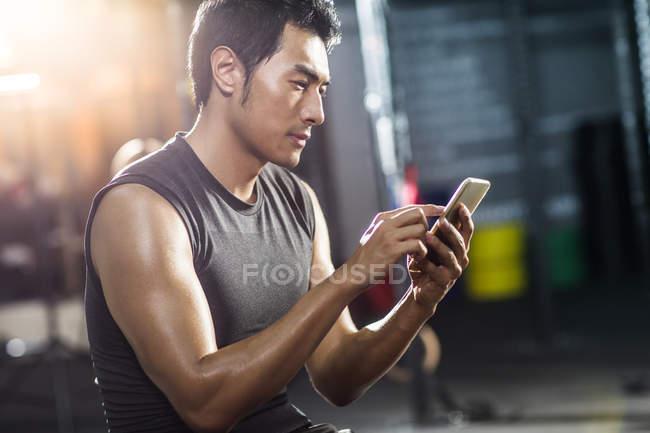 Chinesischer Mann mit Smartphone in Turnhalle — Stockfoto