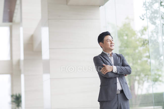 Asian businessman standing with arms folded — Stock Photo