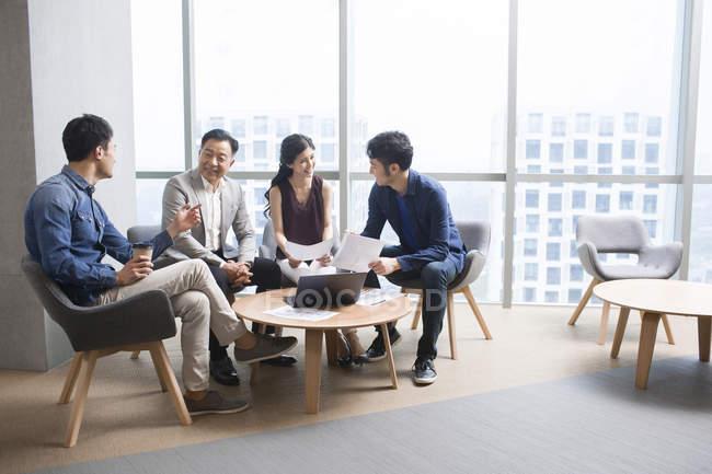 Equipo de empresarios chinos discuten trabajo en reunión - foto de stock