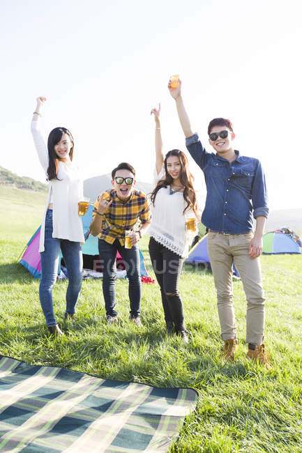 Chinese friends cheering with beer at music festival camping — Stock Photo
