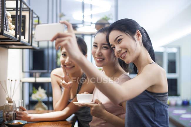 Amis féminins prenant selfie tout en buvant du café dans la cuisine — Photo de stock