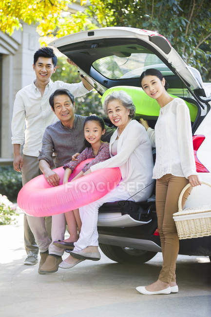 Chinese family sitting in open car trunk with inflatable ring — Stock Photo