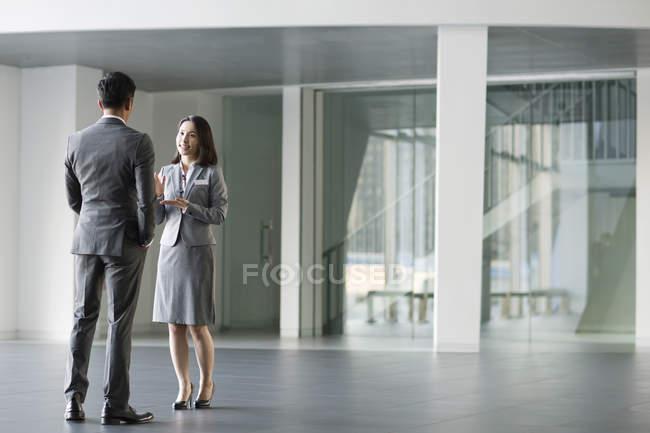 Китайские бизнесмены разговаривают в офисном здании — стоковое фото