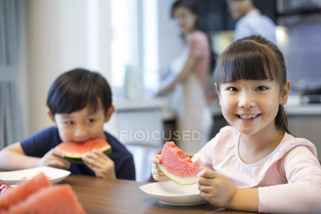 Китайских братьев и сестер, едят арбуз на кухне tableac — стоковое фото