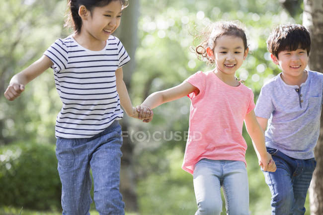 Chinese children holding hands and running in woods — Stock Photo