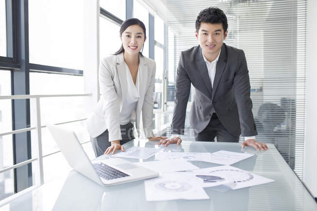 Chinese business people standing in meeting room — Stock Photo