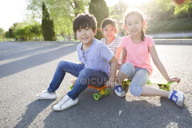 Chinese children sitting on skateboard — Stock Photo