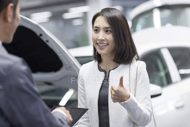 Chinese auto mechanic talking with car owner — Stock Photo