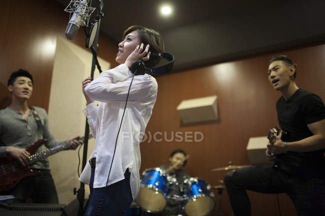 Chinese musical band recording song in studio — Stock Photo