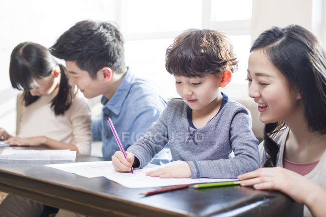Asian parents helping children with homework — Stock Photo