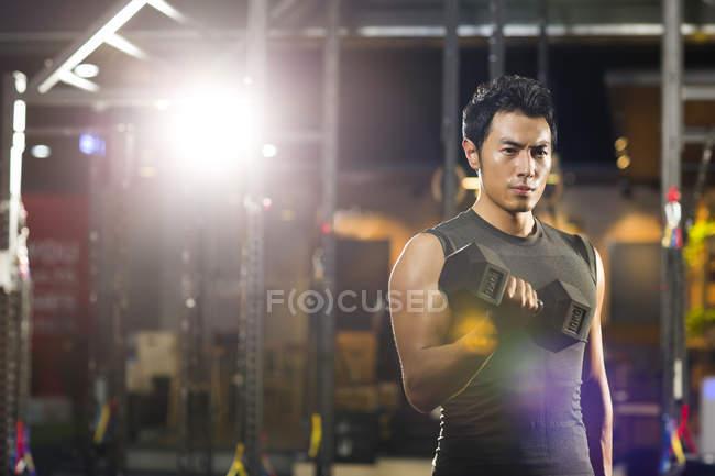 Chinese man lifting weights at gym — Stock Photo