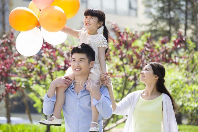 Felice famiglia cinese passeggiando nel parco con palloncini — Foto stock
