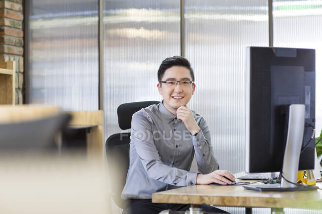 chinese office worker sitting in office selective focus using