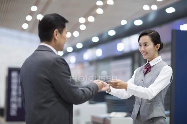 Sonriente azafata China tomando el billete del pasajero masculino - foto de stock