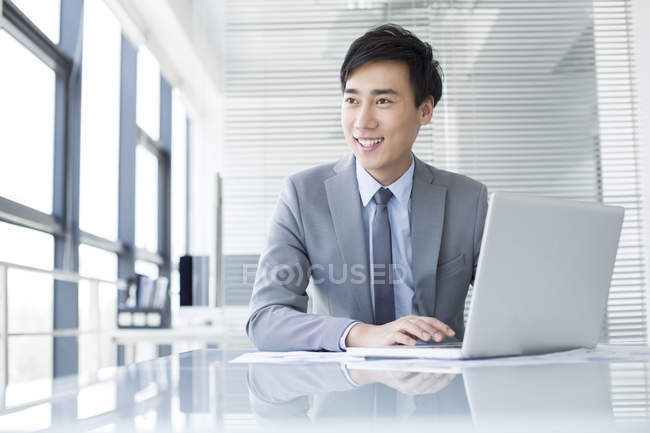 Chinese businessman using laptop in office — Stock Photo