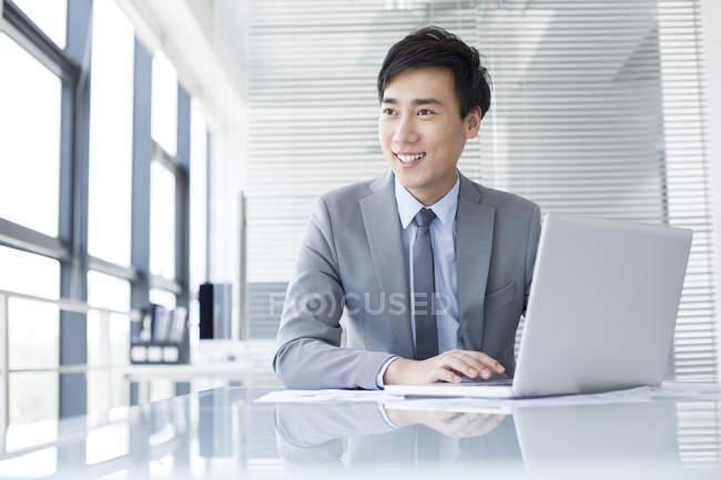 Chinesischer Geschäftsmann mit Laptop im Büro — Stockfoto