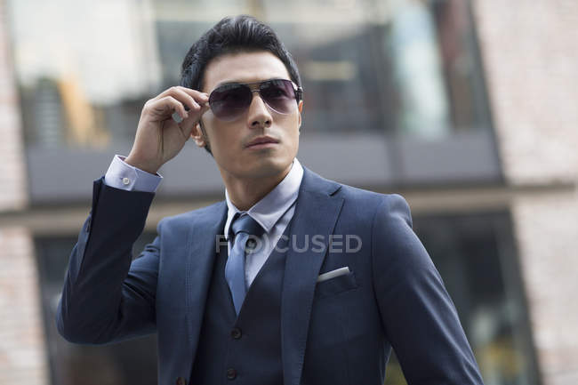 Asian man putting on sunglasses on urban street — Stock Photo