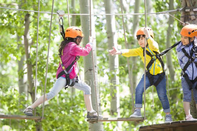 Enfants chinois grimpant sur les arbres dans le parc d'aventure — Photo de stock