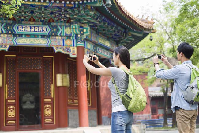 Китайська пара фотографувати з смартфонів в храмі лама — стокове фото