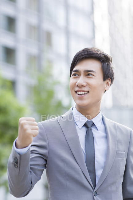 Chinese businessman standing on street and cheering — Stock Photo