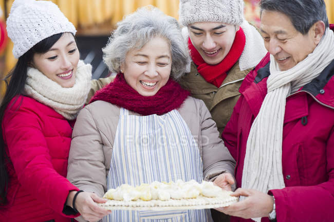 Chinese family standing with traditional dumplings — Stock Photo