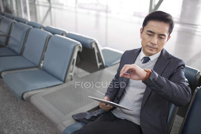 Азиатский мужчина ждет в аэропорту с цифровым планшетом и глядя на часы — стоковое фото
