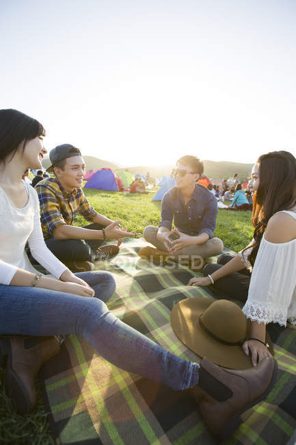Chinese friends sitting on blanket at music festival — Stock Photo
