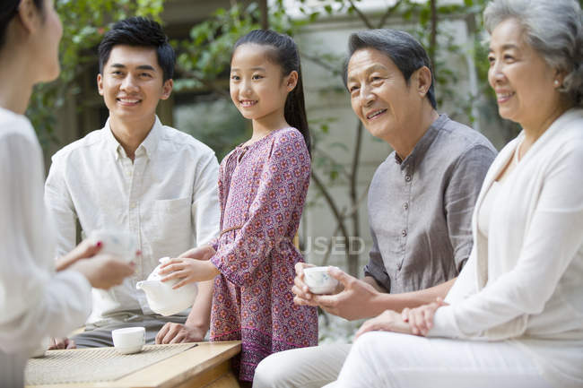 Chinese girl serving tea for multi-generation family in courtyard — Stock Photo
