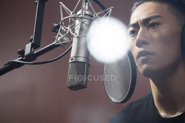Chinese man singing in recording studio — Stock Photo