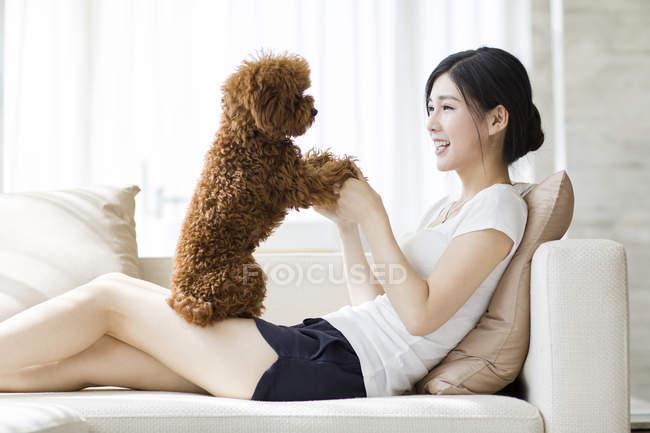 Giovane donna cinese che gioca con barboncino animale domestico sul divano — Foto stock