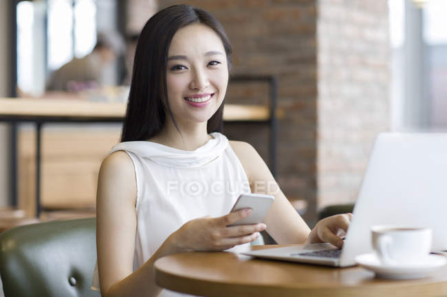 Chinese woman working with laptop and smartphone in cafe — Stock Photo