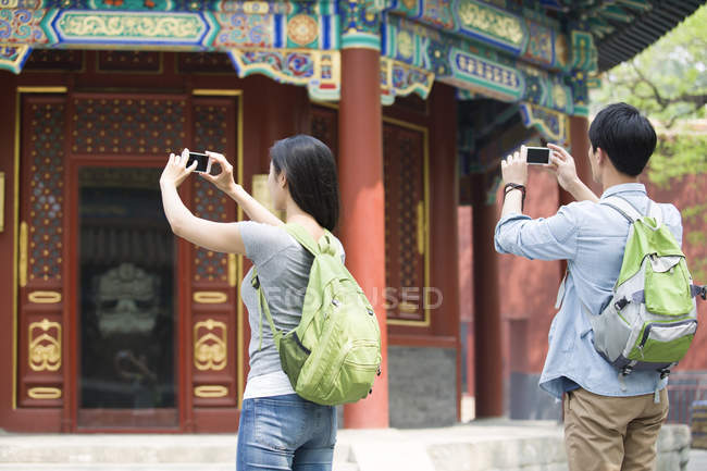 Chinese couple taking pictures with smartphones in Lama Temple — Stock Photo