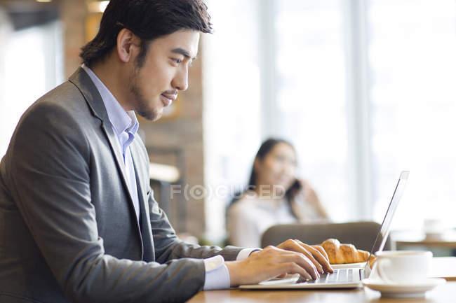 Китайський бізнесмен, робота з ноутбука в кафе — стокове фото