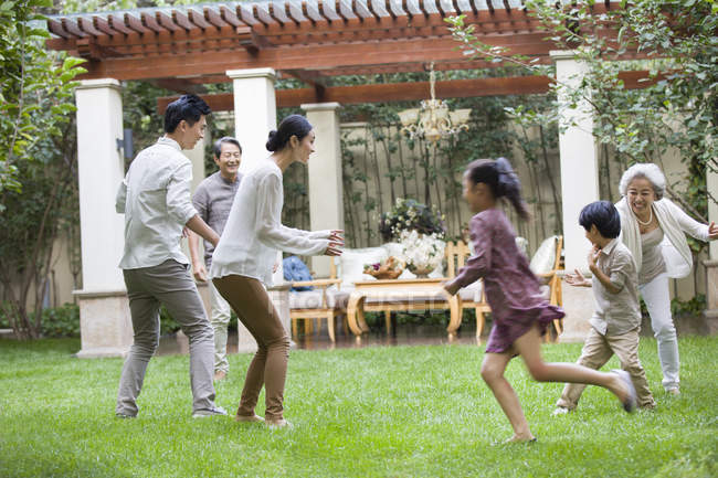Happy Chinese multi-generation family playing together in garden — Stock Photo