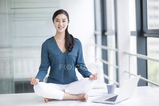 Китаянка медитирует на рабочем столе — стоковое фото