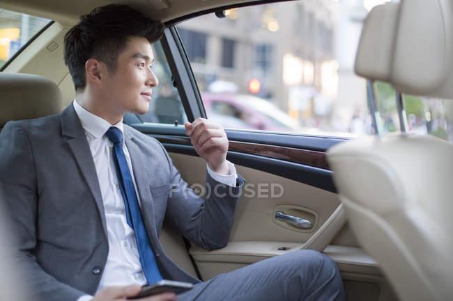 Homme d'affaires chinois assis sur le siège arrière de voiture avec smartphone — Photo de stock