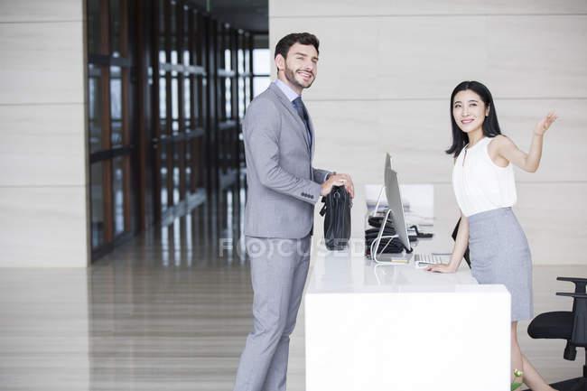 Empresario hablando con recepcionista en edificio de oficinas - foto de stock