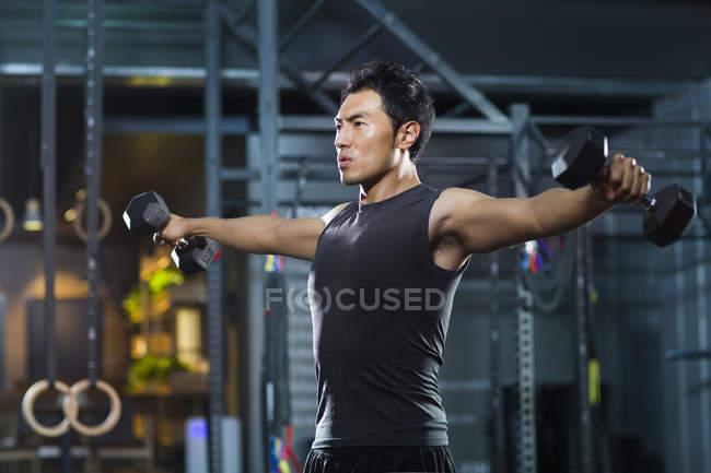 Chinesischer Mann Heben von Gewichten im Fitnessstudio — Stockfoto