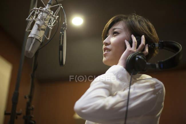 Chinese woman singing in recording studio — Stock Photo