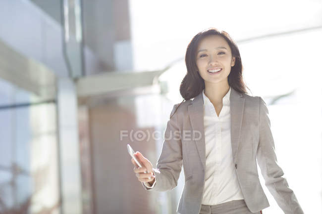 Asian businesswoman walking with smartphone — Stock Photo